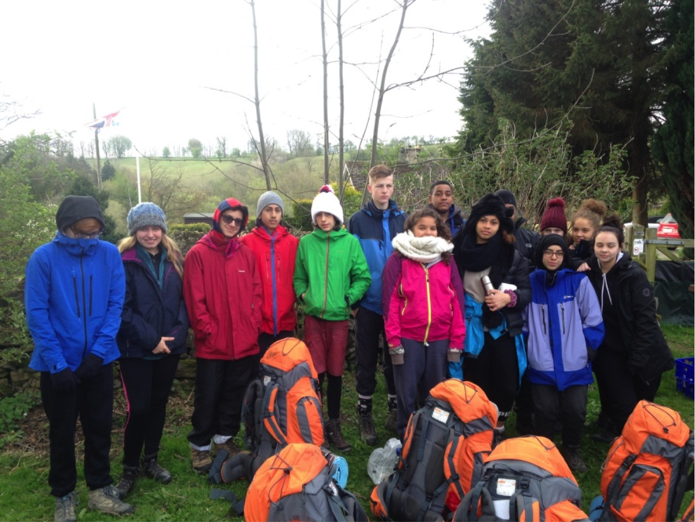 Duke of Edinburgh Group in their wet weather gear stand behind their rucksacks